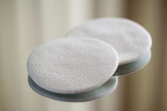 Cotton round cosmetic pads. On reflective surface, close-up macro Royalty Free Stock Photos