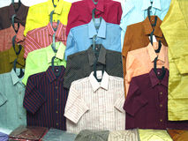 Cotton Shirts. Man's wear: Some colorful cotton shirts on plastic hangers Stock Photos