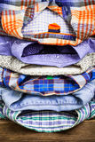 Cotton shirts on a wooden shelf in a clothes store. Stack of colored cotton shirts on a wooden shelf in a clothes store Royalty Free Stock Photo