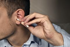 Cotton swab and ear. Closeup man cleaning ear with a cotton bud, health care stock photo