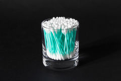 Cotton swabs in clear glass jar on black background Stock Photos