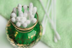 Cotton swabs in a green glass vase Royalty Free Stock Images