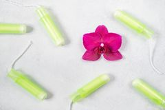 Cotton tampons with orchid on light grey background. Concept of critical days, menstruation or woman`s health. Top view, flat lay. Cotton tampons with magenta royalty free stock image