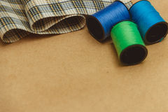 Cotton thread bobbins and cloth on paper craft with copyspace, sewing material. Royalty Free Stock Images