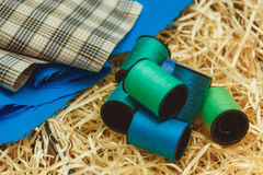 Cotton thread bobbins and cloth on wooden shavings, sewing material. Stock Photography