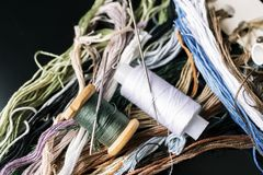 Cotton thread for embroidering a cross and needles on a black background.  Stock Image