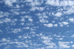 Cotton wool clouds. Dappled skies, white cotton wool clouds on a crystal blue sky. A streak of white shows the path of an aeroplane, heading off to distant Stock Image