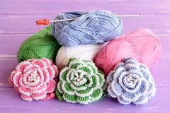 Cotton yarn skeins, hook and bright knitted flowers on wooden background lilac. Home decor crochet project Stock Photo