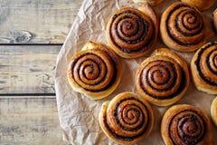 Cottura casalinga dolce di natale Panini dei rotoli di cannella con cacao che riempie sulla carta pergamena Dessert dello svedese Fotografia Stock