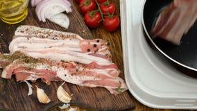 Cottura casalinga Il petto sottilmente affettato di manzo o della carne di maiale, spezie spolverate è preso con le tenaglie dell stock footage