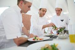 Cottura cuoco unico e del personale in ristorante Fotografie Stock Libere da Diritti