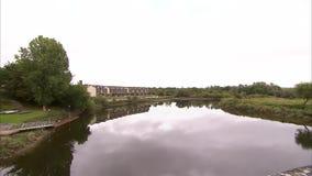 Cottura da un fiume calmo ad un vecchio ponte di pietra stock footage