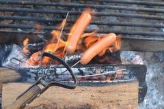 Cottura degli hot dog sopra fuoco di accampamento Immagine Stock