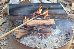 Cottura degli hot dog sopra fuoco di accampamento Fotografia Stock