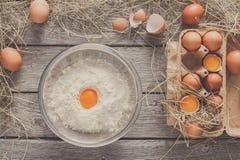 Cottura degli ingredienti per cuocere, le uova e la farina Immagini Stock
