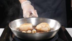 Cottura dei frutti di mare in ristorante Cuoco unico professionista che mescola padella con i pettini e le verdure nel condimento stock footage