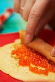 Cottura dei pancake con il caviale Immagine Stock