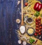 Cottura del concetto della pasta con i pomodori, parmigiano, pepe, spezie, farina, aglio, cucchiaio di legno, confine, area di te Immagini Stock