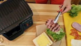 Cottura del panino nella cucina La vista superiore della mano con le tenaglie prende un pezzo di carne appena-tostato caldo dalla archivi video