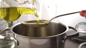 Cottura del pasto in un vaso Bottiglia di olio vergine extra che versa dentro al vaso per la cottura del pasto stock footage