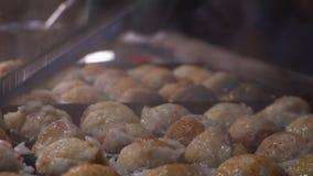Cottura del piatto giapponese tradizionale autentico Takoyaki al mercato asiatico di notte della via Cucina del Giappone stock footage