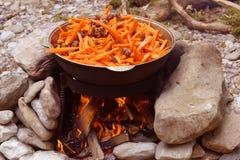 Cottura del pilaf sopra un fuoco di accampamento Immagini Stock Libere da Diritti