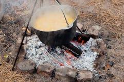 Cottura del porridge in una casseruola sul fuoco Immagini Stock