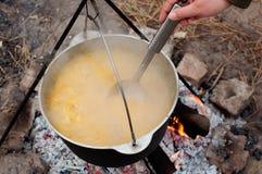 Cottura del porridge in una casseruola sul fuoco Fotografia Stock
