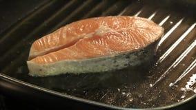 Cottura del salmone in una pentola della colata del ferro archivi video