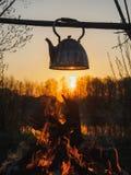 Cottura del tè su un fuoco in un bollitore al tramonto immagine stock libera da diritti