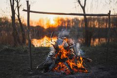 Cottura del t? su un fuoco in un bollitore al tramonto immagine stock