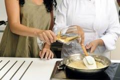 Cottura del vino di versamento del risotto fotografie stock