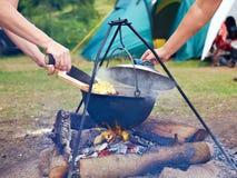 Cottura dell'alimento sopra fuoco di accampamento Fotografie Stock Libere da Diritti