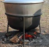 Cottura dell'alimento sopra un fuoco di accampamento Immagine Stock