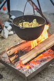 Cottura dell'alimento su un fuoco in un calderone fotografia stock libera da diritti