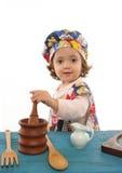 Cottura della bambina vestita come cuoco unico Immagine Stock Libera da Diritti