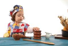 Cottura della bambina vestita come cuoco unico Fotografie Stock Libere da Diritti