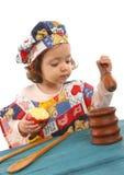 Cottura della bambina vestita come cuoco unico Fotografie Stock