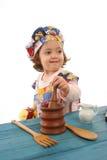 Cottura della bambina vestita come cuoco unico Immagini Stock