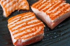 Cottura della bistecca di color salmone sulla griglia Fotografia Stock Libera da Diritti