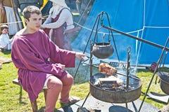 Cottura della carne in una rimessa in vigore medioevale Fotografie Stock