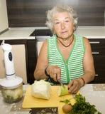 Cottura della donna anziana Fotografia Stock