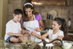 Cottura della famiglia della figlia del figlio della madre in una cucina immagine stock libera da diritti