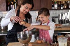Cottura della figlia e della madre nella cucina Fotografie Stock