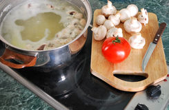 Cottura della minestra con il pomodoro ed i funghi freschi immagine stock libera da diritti