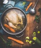 Cottura della minestra di pollo, vaso con il brodo di pollo e siviera su fondo di legno rustico scuro con gli ingredienti delle v immagine stock libera da diritti