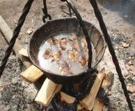 Cottura della minestra su fuoco di accampamento Fotografie Stock