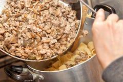 Cottura della pasta con carne ed i funghi Fotografia Stock