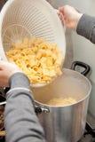 Cottura della pasta con una colapasta Immagine Stock Libera da Diritti