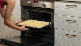 Cottura della pizza in forno elettrico Donna che fa pizza casalinga Pizza di cottura della donna a casa la donna nella cucina pre stock footage